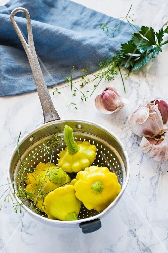 Yellow patty pan squash in a colander