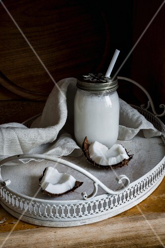Vegan coconut milk in a screw-top jar with a straw on a tray