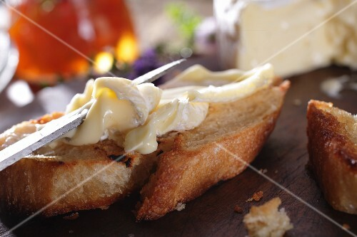 A slice of baguette being spread with Camembert
