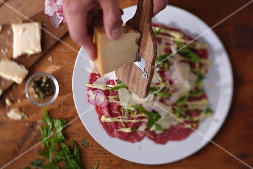 Parmesan being grated over beef carpaccio