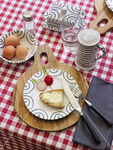 A table laid for supper with bread, butter, radishes, eggs and beer