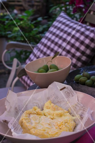 Le Montagnard (soft cheese from Vogesen) with olives in a garden