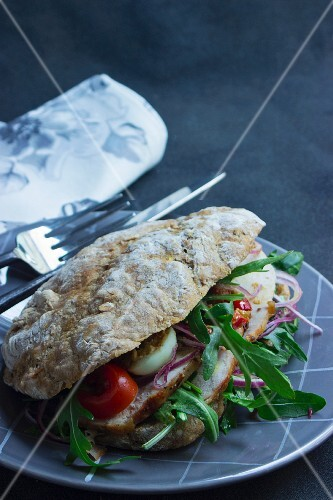 Ciabatta sandwich with roast pork, rocket, hard-boiled eggs and tomatoes