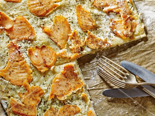 Freshly baked tart flambé with salmon, sliced, on a baking tray