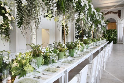 Festive wedding table with green and white flower arrangements in hall