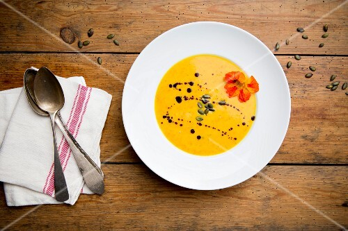 Cream of pumpkin soup with pumpkin seeds, pumpkin seed oil and nasturtium flowers