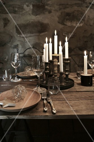 Christmas in a wine cellar: a place setting on a rustic wooden table with wine and candles