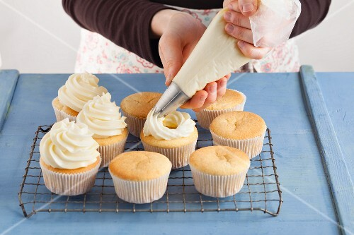Meringue frosting being piped onto cupcakes