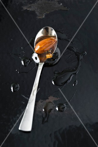 An almond preserved in honey on a spoon