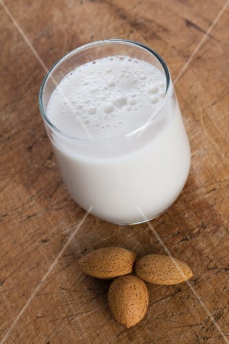 A glass of almond milk and whole almonds