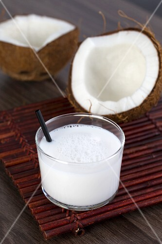 A coconut milk drink in a glass with a straw