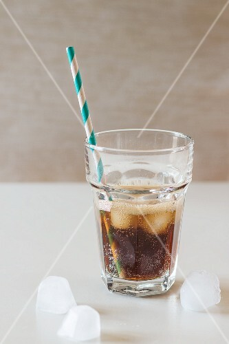 A glass of cola with ice cubes and a retro straw