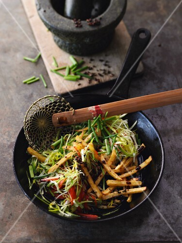Sweet-and-sour fried potatoes in a wok