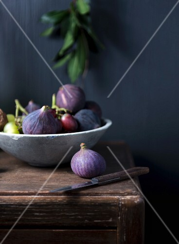 A bowl of fresh figs and grapes