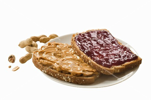 A slice of bread spread with peanut butter and another spread with jam