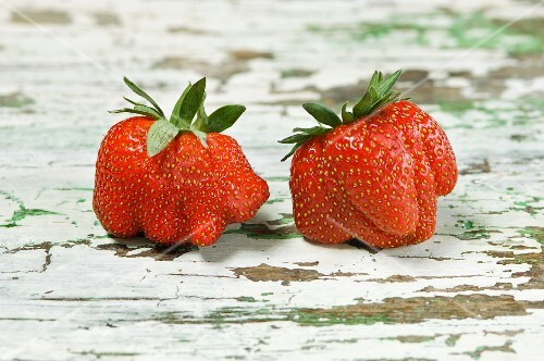 Two strawberries on a wooden table