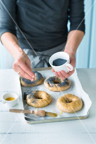 Bagels being sprinkled with poppy seeds for baking