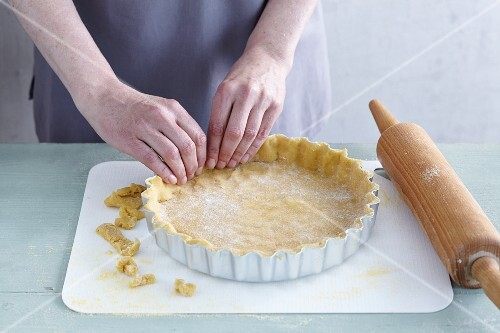 Gluten-free shortcrust pastry being pushed into a baking dish