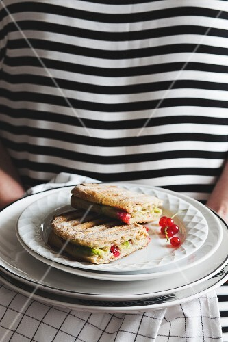 A woman serving a panini with avocado and redcurrants