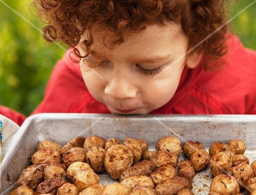 A red-haired boy sniffing at a tray of roast potatoes