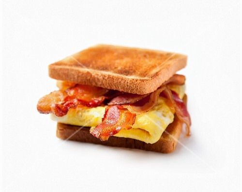 A toasted bacon and egg sandwich on a white surface