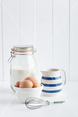 Eggs, flour, a jug of milk and whisk
