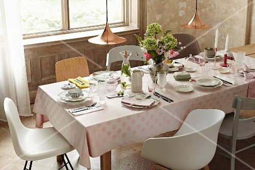 A festively laid table with elegant porcelain on a pastel pink spotted tablecloth