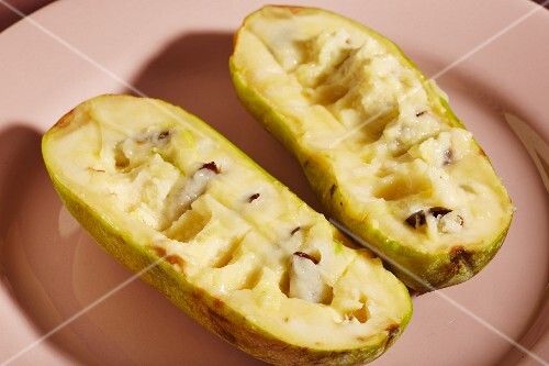 Ripe pawpaws, halved, on a pink plate