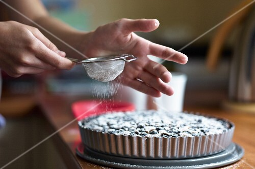 Blueberry tart being dusted with icing sugar