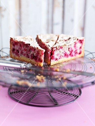 Three slices of redcurrant cake with meringue on a cake stand
