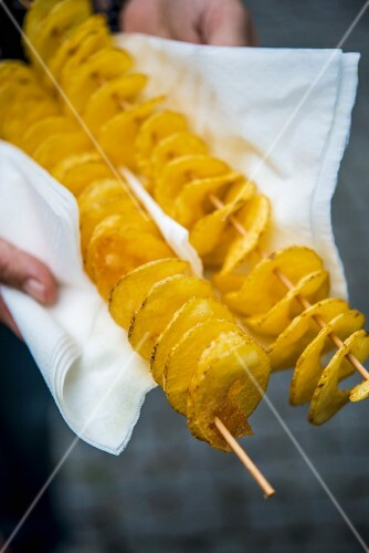 Hands holding potato spirals on wooden skewers in a napkin