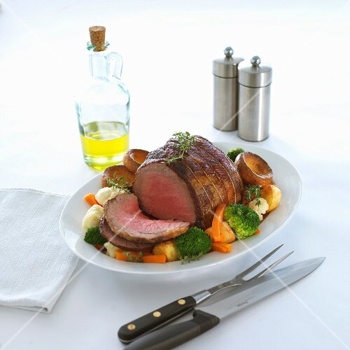 A joint of roast beef with vegetables and Yorkshire puddings