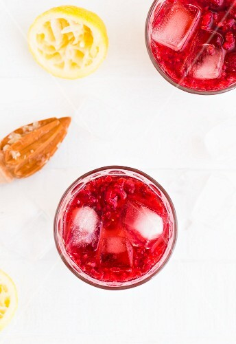 Raspberry lemonade with lemon juice and ice cubes