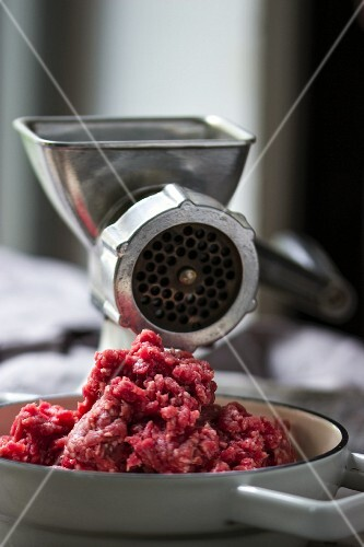 Freshly minced meat and a mincing machine