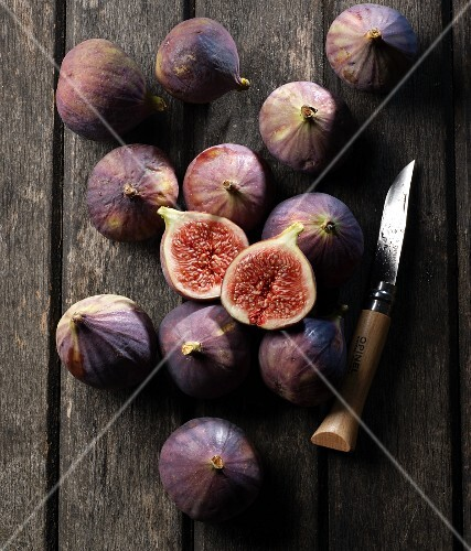 Figs on a wooden table, one slice, with a knife