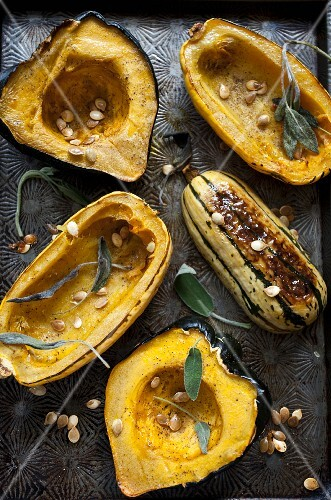 Roasted hollowed-out pumpkin with pumpkin seeds and sage on an antique baking tray
