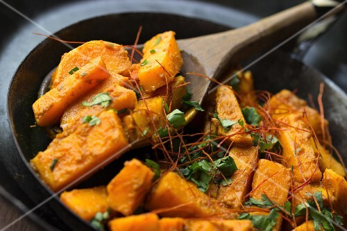Sweet potato curry with coriander and African wooden bowl with a wooden spoon