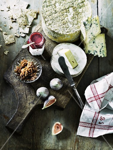 An arrangement of cheese with lingonberry jam, walnuts and figs