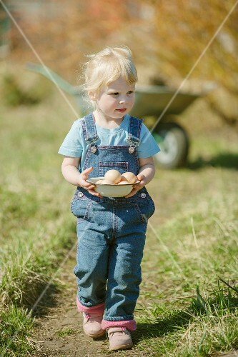 A little girl holding a bowl of eggs in a field