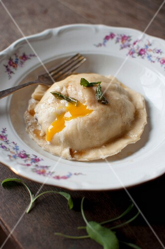 Ravioli with a mushroom and ricotta filling and egg yolk served with sage butter