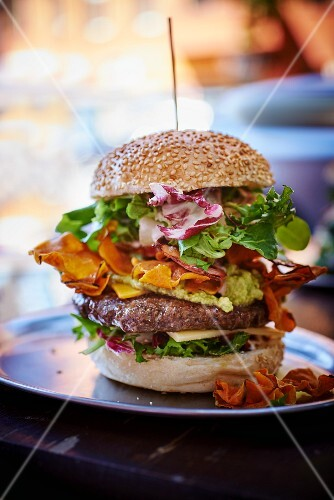 A burger with guacamole and sweet potato chips