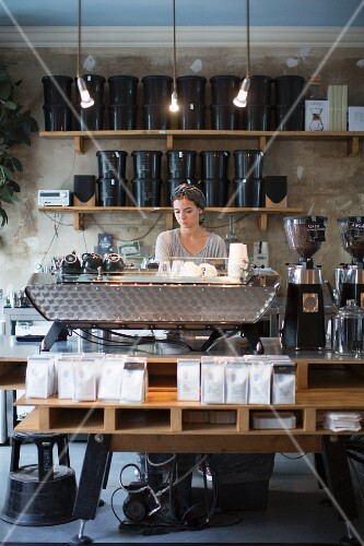 A young woman behind a bar at Bonanza Coffee Heroes, café and roastery