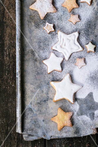 Glazed star-shaped Christmas biscuits with icing sugar on a baking tray