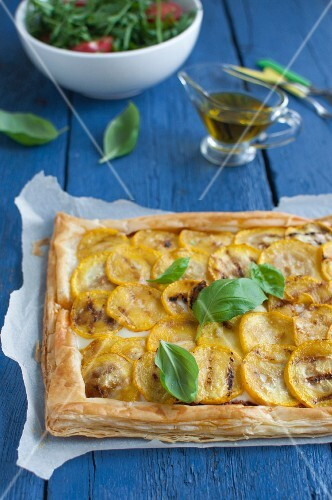 A puff pastry tart with yellow courgettes, pesto rosso, cheese and basil