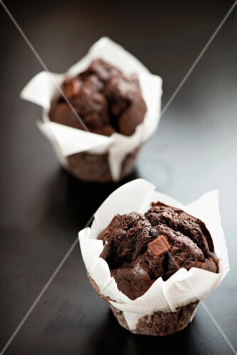 Two chocolate fudge muffins in white paper