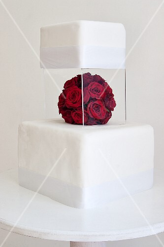 A two-tier wedding cake with a perspex stand and red rose decorations