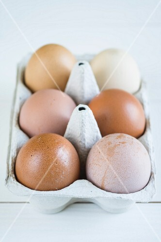 Various brown eggs in an egg box