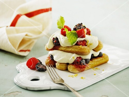 A layered dessert with sponge fingers, berries and mascarpone cream