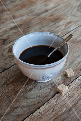 Black coffee in a ceramic bowl with a spoon