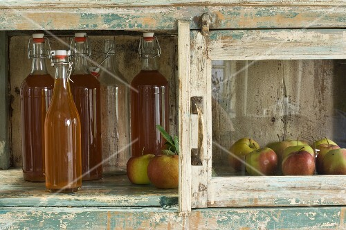 Several bottles of apple juice and apples (variety 'Jonagold') in rustic cupboard